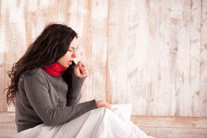 Frau mit Erkältung hustet